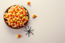 Bowl With Tasty Halloween Candies On Color Background