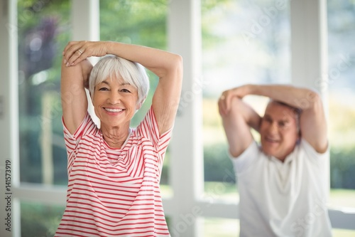 Leinwand Poster  Senior couple performing stretching exercise at home