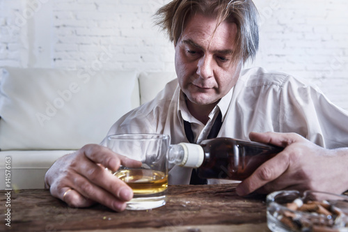 depressed alcoholic businessman with loose necktie wasted and drunk drinking whi Fototapet