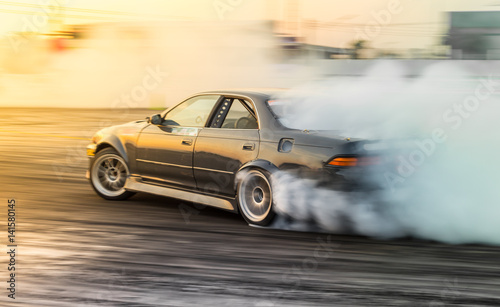 Foto Motion automobile blur, Auto vehicle race car drift racing on speed track with lot of smoke tire burn