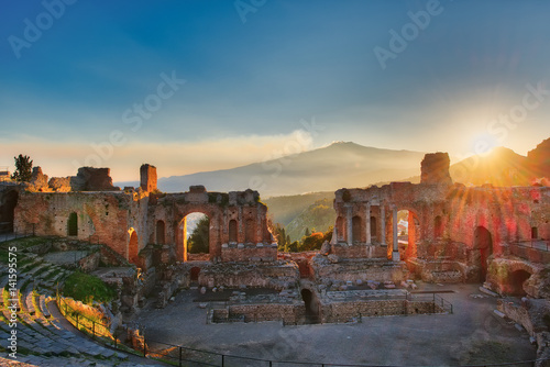 Fotografie, Obraz  Particular of Ancient theatre of Taormina with Etna erupting volcano at sunset