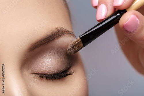 Obraz makeup artist apply makeup brush for eyes. makeup for young girl. brown eye shadow. close up - fototapety do salonu