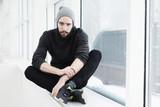 Fototapeta Łazienka - Young bearded man with crossed legs sitting on window sill