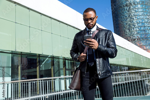 Young businessman with phone outdoors