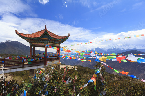 Meili snow mountain with Prayer flags and Chinese style roof, Deqing, Yunnan, China