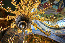 Vintage Iron Chandelier With Floral Twisted Ornament Gold Color Close-up In Of St. Isaac's Cathedral, Saint Petersburg, Russia.