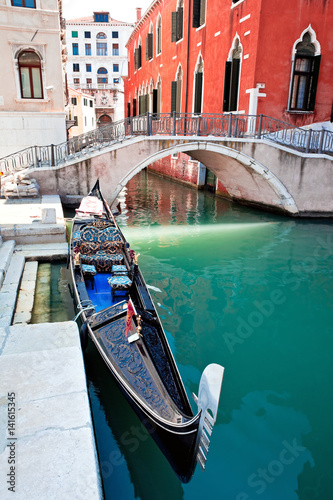 Gondola on Venice canal with bridge and houses standing in water