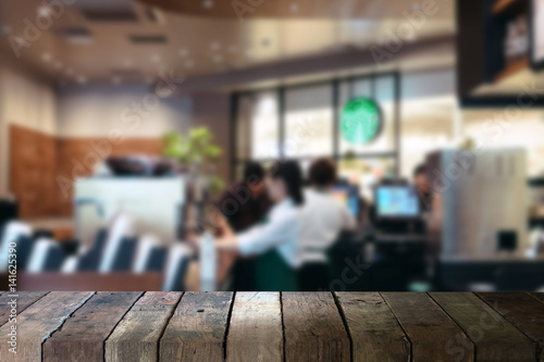 Fotografía  image of wooden table in front of abstract blurred background of coffee shop caf