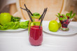 Red and green healthy smoothies with fresh ingredients on table.
