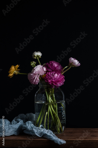 Fotografie, Obraz  Dark and moody image of colorful ranunculus flowers