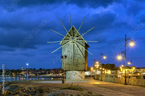 Poster Molens Old windmill at the entrance to the Old Town of Nessebar in evening, Bulgaria