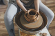 Midsection of female potter making pot with clay in workshop