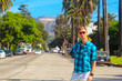 Young man standing on the Hollywood boulevard with a Hollywood sign on the hills and palms just behind him. Man pointing at the sign.