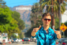 Cool Guy Standing On The Boulevard Showing Thumbs Up With A Hollywood Sign Behind Him. Beautiful Perfect Life.