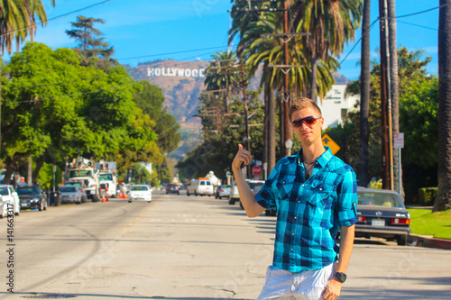 Photo  Young man standing on the Hollywood boulevard with a Hollywood sign on the hills and palms just behind him
