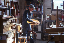 Carpenter Removing Sawdust From Wooden Stool In Workshop