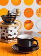 A Cup of coffee and grinder on an orange background.
