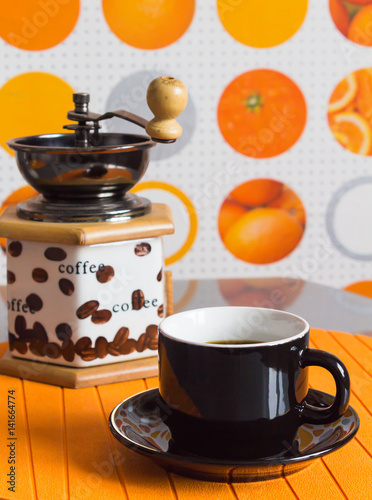 Poster Café en grains A Cup of coffee and grinder on an orange background.