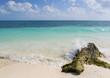 Beautiful scenery from the Caribbean sea. Big rock on the beach, splashing wave. Turquoise water.