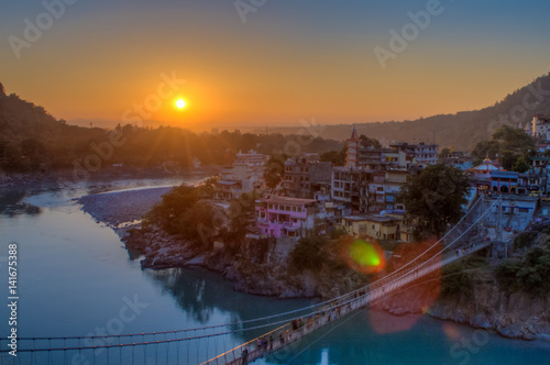 View of River Ganga and Lakshman Jhula bridge at sunset with a blue sky and colorful houses Wallpaper Mural