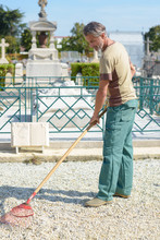 Man Raking Gravel In Cemetery
