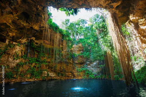 Tuinposter Mexico Sunbeams penetrating at Ik-Kil cenote inlet