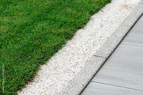 Tuinposter Groene gravel in landscape design is poured near the lawn