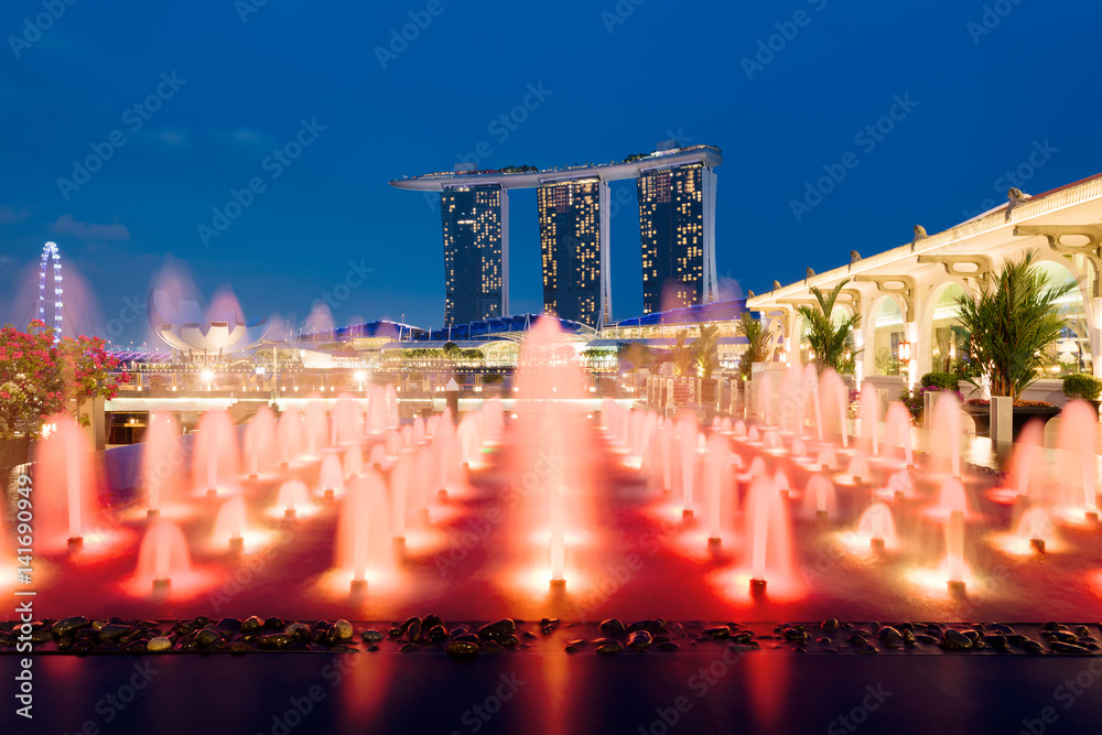 Plagát  Marina Bay Sands and a colorful fountain at night in Singapore.