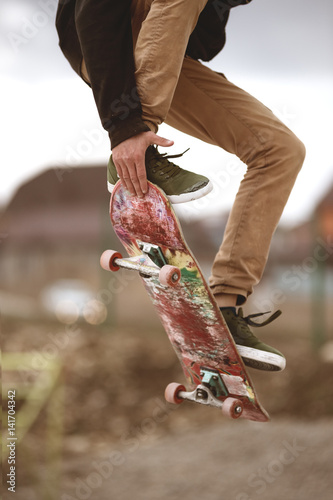 Close-up of skateboarders foot while skating in skate park Fototapeta