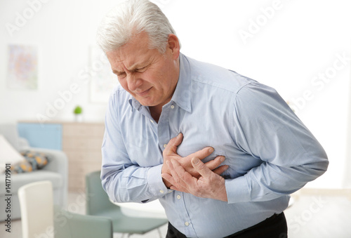 Fotografia Man with chest pain suffering from heart attack in office