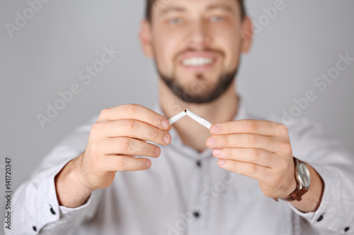 Quit smoking concept. Man breaking cigarette, on light background Wallpaper Mural
