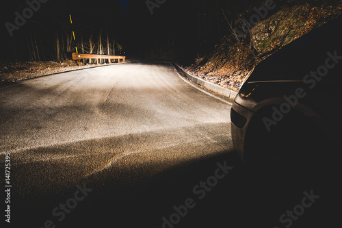Obraz the headlights of a car on mountain road in the night - concept driving safety - fototapety do salonu