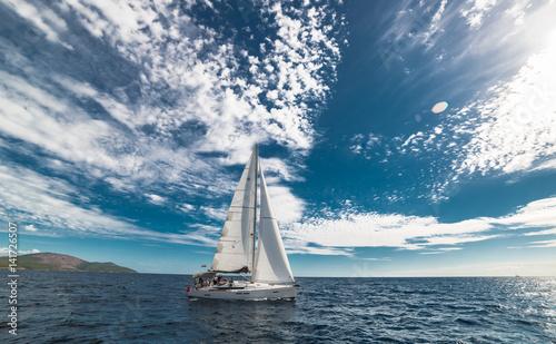 яхта с белыми парусами под глубоким, синим облачным небом Canvas Print