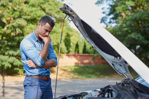 Zdjęcie XXL Zaakcentowana mężczyzna pozycja łamanym samochodem na drodze