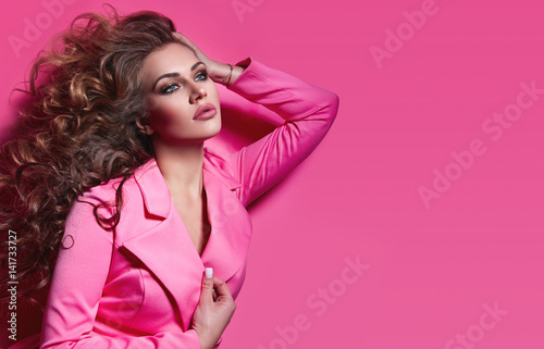 Fotografía  Beautiful fashionable girl haired with long curly hair in a pink jacket