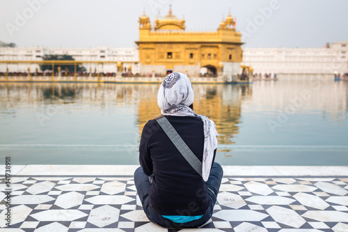 Fényképezés  Girl sitting front of the Golden Temple in Amritsar, India