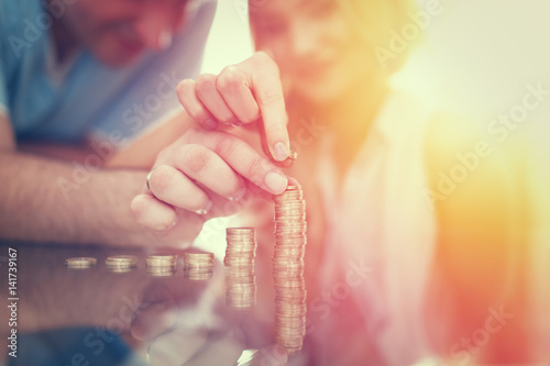 Fototapeta Young couple building money column from coins in sunset obraz