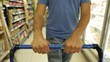 Consumer person shopping at grocery store. POV of man walking with shopping cart
