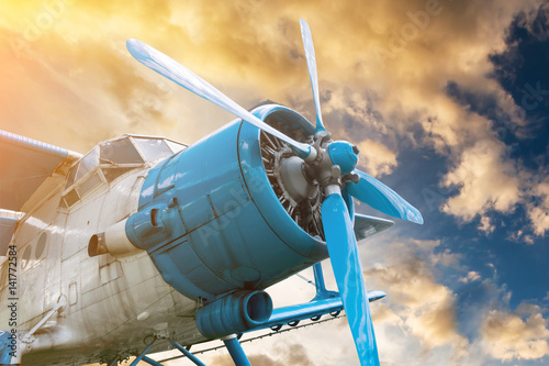 Poster  plane with propeller on beautiful bright sunset sky background