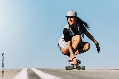Beautiful skater woman riding on her longboard.
