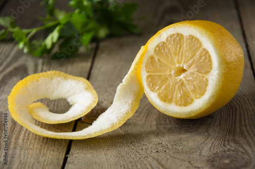 Half peeled fresh lemon on a wooden table with green herbs in the background