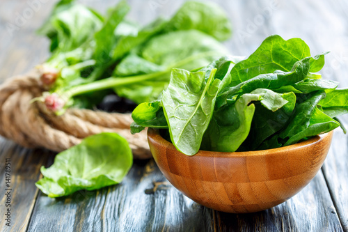 Fresh spinach leaves in a wooden bowl.