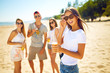 Beautiful girl with glasses is holding a bottle with beer in her hands. Group of friends hanging out with beer at the beach. Excellent sunny weather. Beautiful figures. Super mood. Summer concept