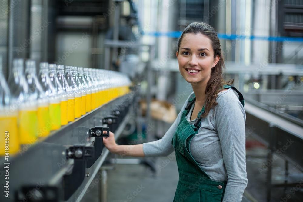 Fototapeta Female factory worker standing near production line