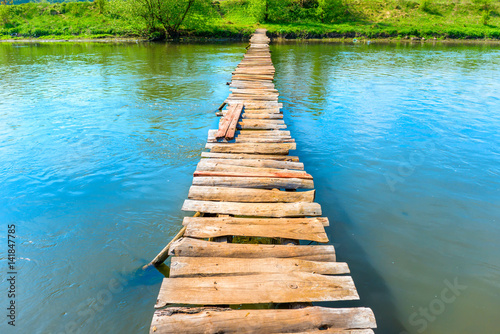 Foto  Old wooden bridge through the river