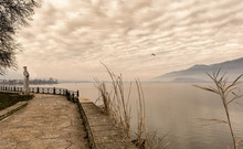 Foggy Afternoon On Lake Pamvotis. Empty Road For Pedestrians And Bicycles .Ioannina ,Greece.Sepia Tone