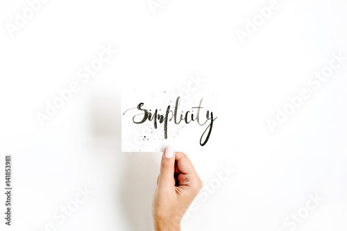 Fotografie, Obraz  Minimal pale composition with girl's hand holding card with word Simplicity written in calligraphic style on paper on white background