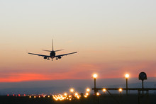 Plane Lands At An Airfield On The Background Of Sunset