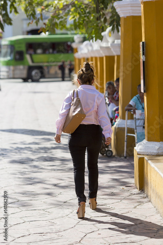 Business woman walking in the streets of Valladolid, Mexico. She is wearing stylish business outfit.