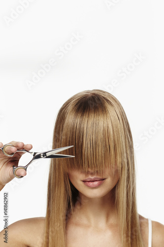 Fotografie, Obraz  Beautiful blond about to cut fringe, studio